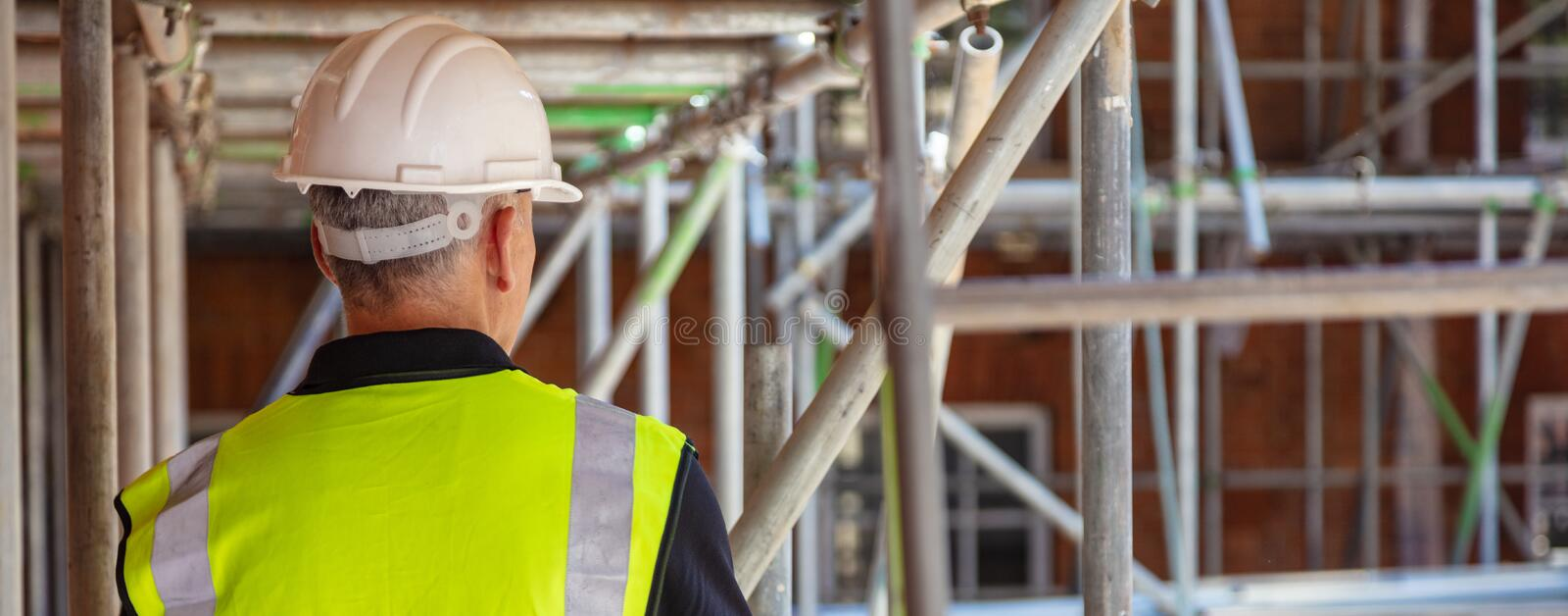 Rear View of a Construction Worker on Building Site. Rear view of male builder construction worker on building site wearing hard hat and hi-vis vest panoramic royalty free stock images