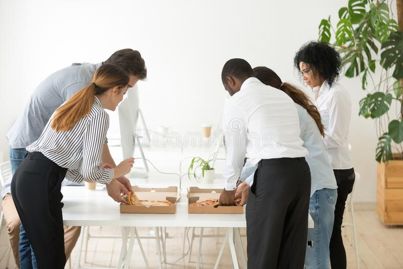Rear view at corporate employees team sharing pizza in office royalty free stock images
