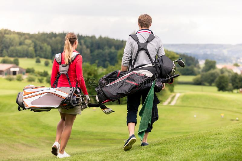 Rear view of couple carrying golf bag stock photography