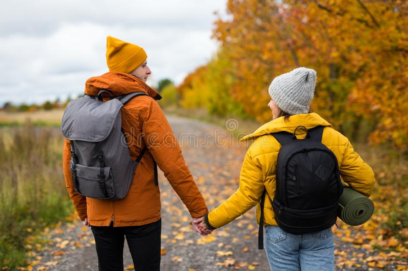 Rear view of couple hikers with backpacks walking in forest. Rear view of couple hikers with backpacks walking in autumn forest royalty free stock photos
