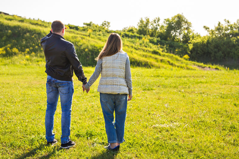 Rear view of couple holding hands walking in autumn countryside royalty free stock photos