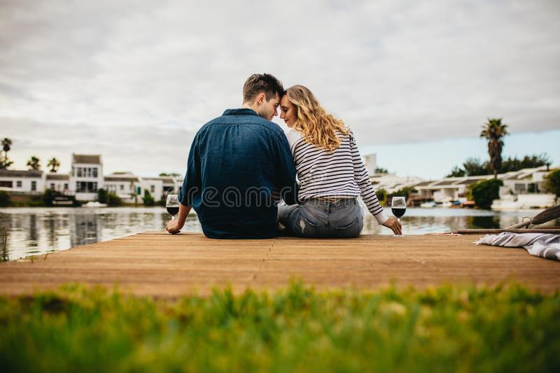 Rear view of a couple in love sitting together touching their heads near a lake. Couple on a day out sitting together holding wine royalty free stock photos