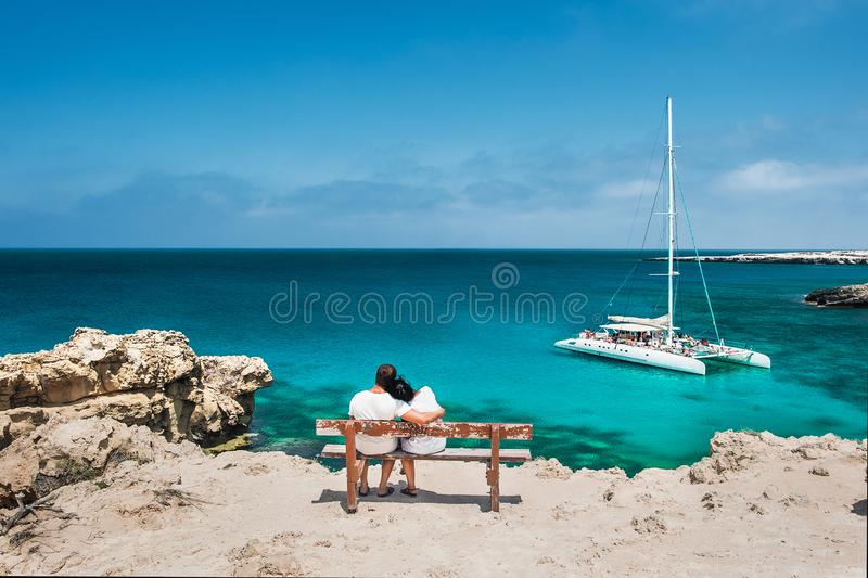 Rear view of a couple in love on vacation. Honeymoon traveller couple hugging on a wooden bench and enjoys their tropical holiday. Wedding travel. Young happy royalty free stock image