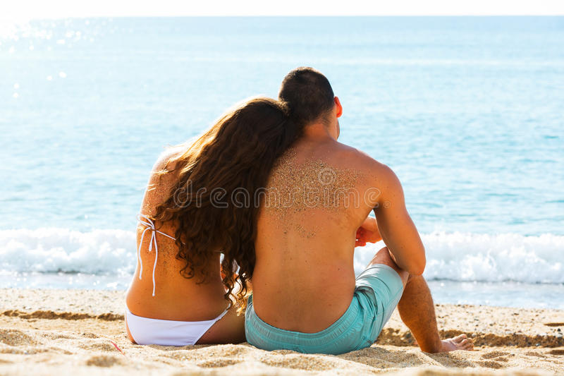 Rear view couple sitting at beach. Rear view young couple sitting at sandy beach royalty free stock images