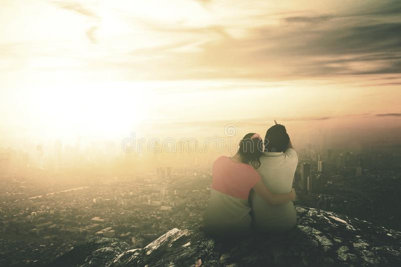 Rear view of couple sitting on top of the mountain to see sunset stock photography