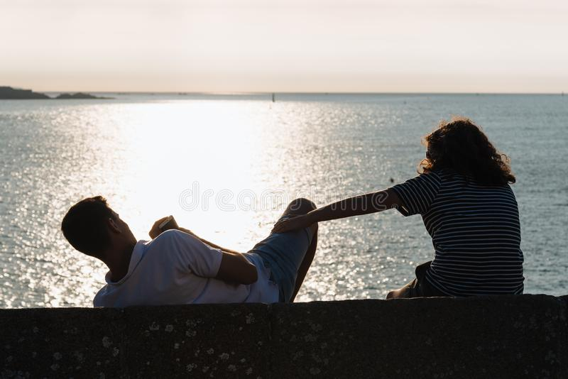 Rear view of couple sitting on wall during sunset. Rear view of couple fooling around while sitting on wall during sunset against ocean royalty free stock photo