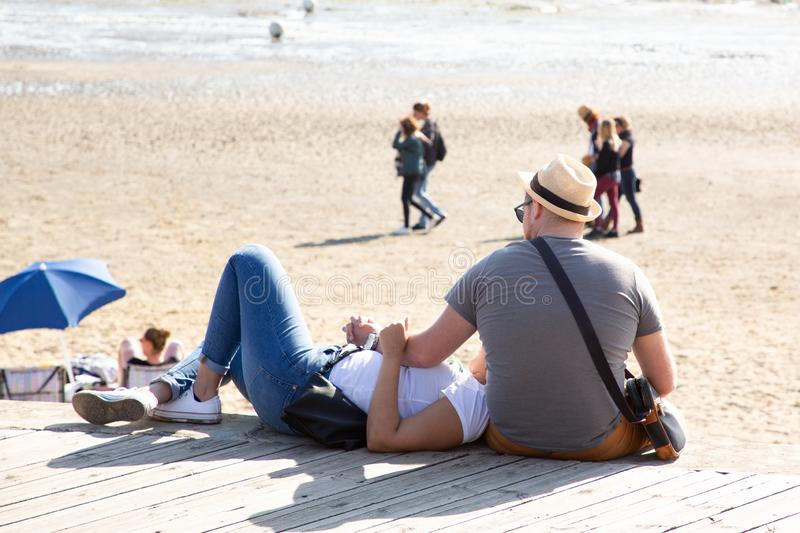 Rear view of couple sitting on a wooden by sea beach stock photos
