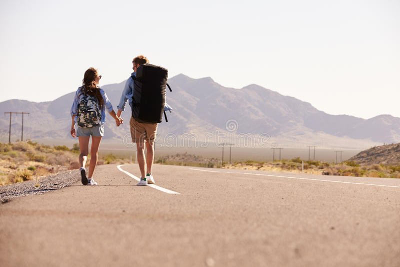 Rear View Of Couple On Vacation Hitchhiking Along Road stock photo
