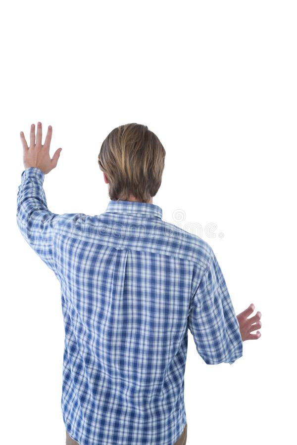 Rear view of creative businessman using imaginary screen. Against white background stock images
