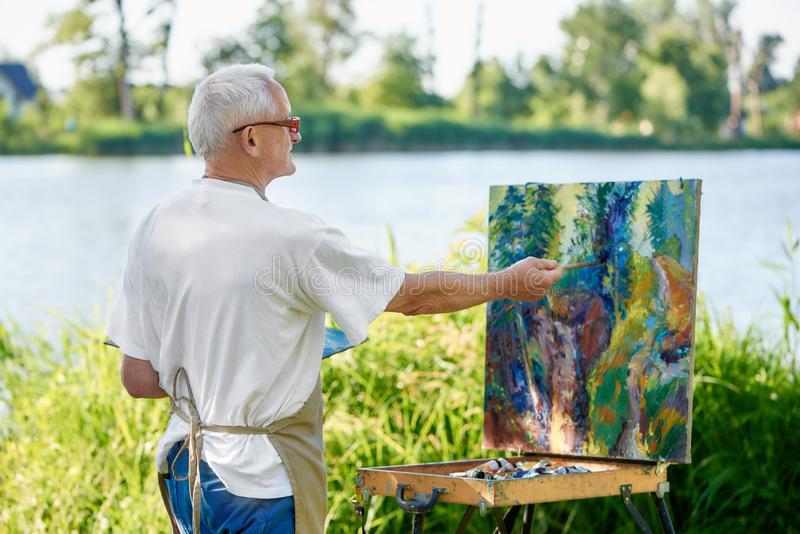 Rear view of creative painter paints colorful abstract painting on open air. stock image
