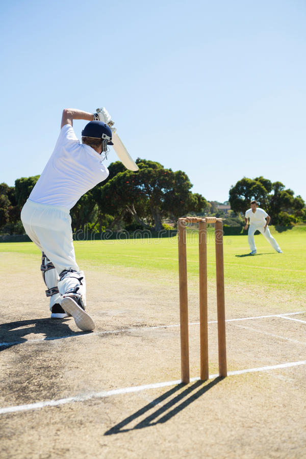 Rear view of cricket player batting while playing on field royalty free stock photos