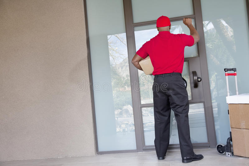 Rear view of a delivery man with packages knocking at door. Rear view of a delivery men with packages knocking at door royalty free stock photos