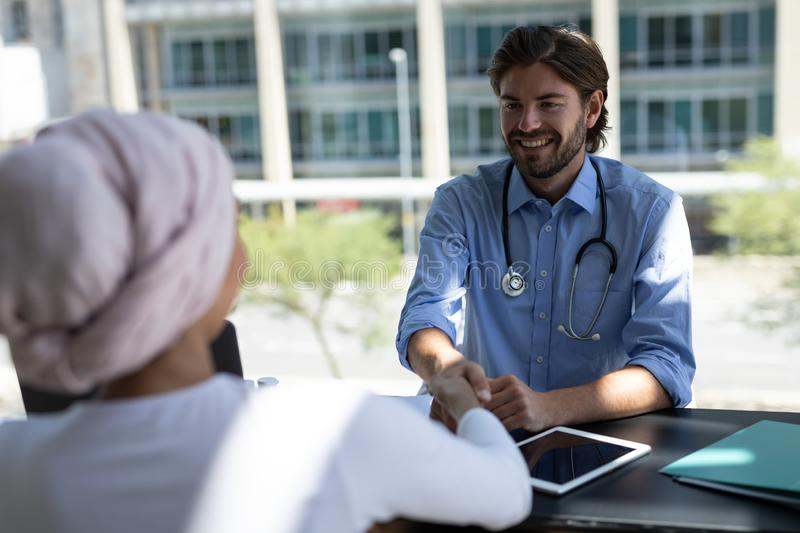 Disabled mixed-race woman shaking hands with Caucasian male doctor stock image