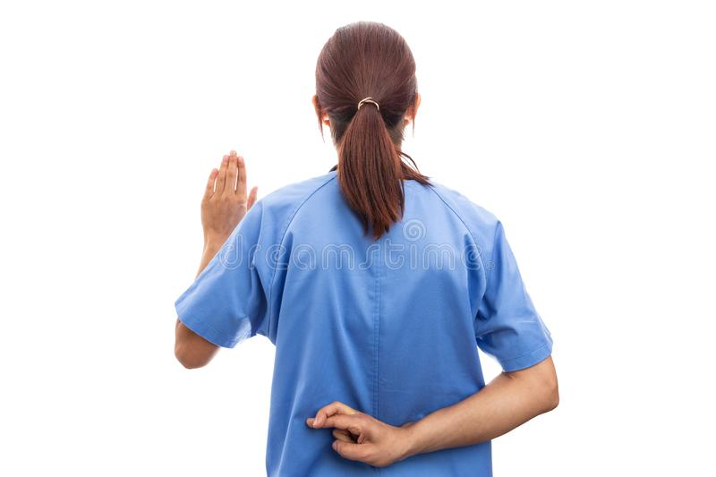 Rear view of dishonest woman nurse or doctor making swear gesture. stock image