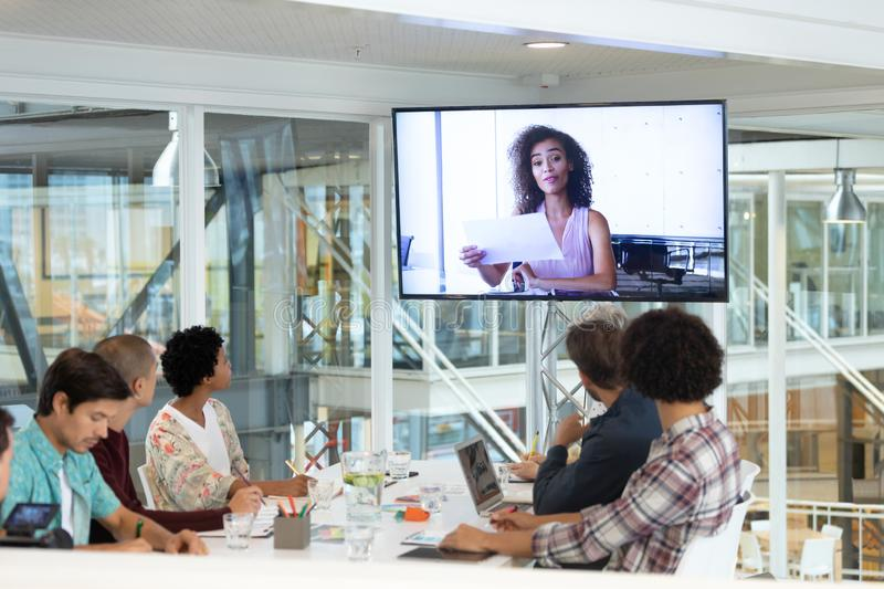 Business people attending video conference at conference room in a modern office. Rear view of diverse business people attending video conference at conference royalty free stock photo