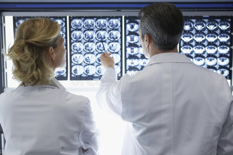 Rear View Of Doctors Discussing Brain Scans. Rear view of a male and female doctors discussing brain scans in hospital stock image