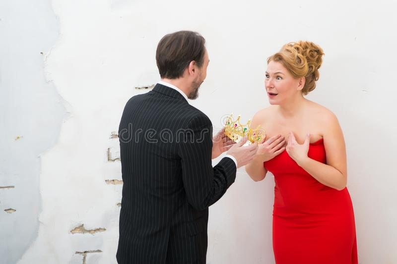 Rear view of elegant man presenting golden crown to his admirable wife stock image