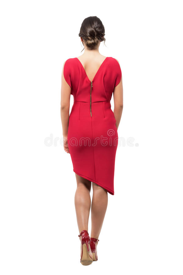 Rear view of elegant woman with bun hairstyle in red evening dress walking away royalty free stock photos