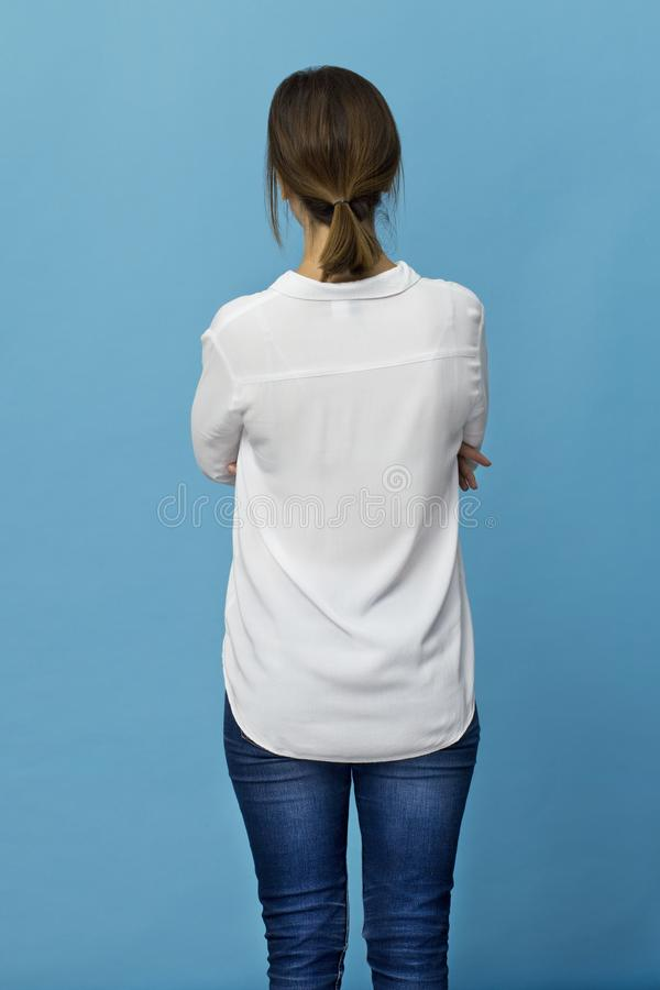 Rear view of elegant young woman wearing white shirt and jeans. Young woman with brown hair back portrait. Rear view on blue royalty free stock photography