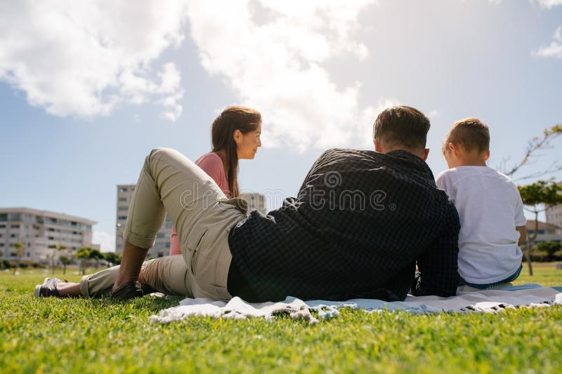 Family out for a picnic in a park. Rear view of a family sitting in a park for picnic. Couple with their child having a day out royalty free stock image