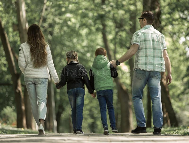 Rear view. family with two children walking hand in hand in the Park. stock photos
