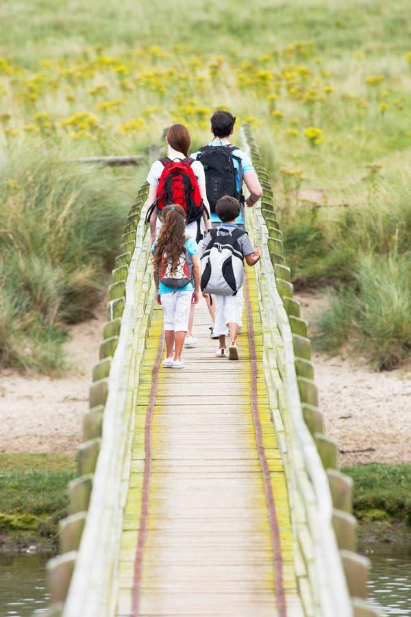 Rear View Of Family Walking Along Wooden Bridge royalty free stock photo