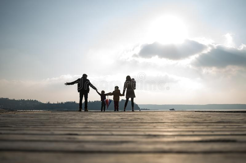 Rear view of father and mother with children holding hands royalty free stock image