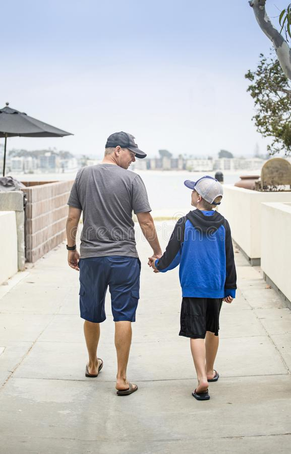 Father and Son walking hand in hand together on the sidewalk. Rear view of a father and son walking together hand in hand along a sidewalk. Talking to each other stock images