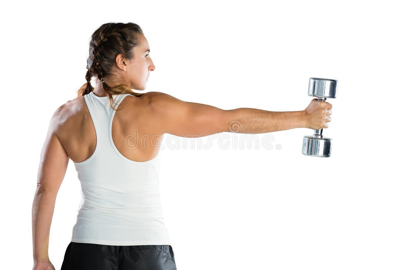Rear view of female athlete exercising with dumbbell. While standing against white background stock photos