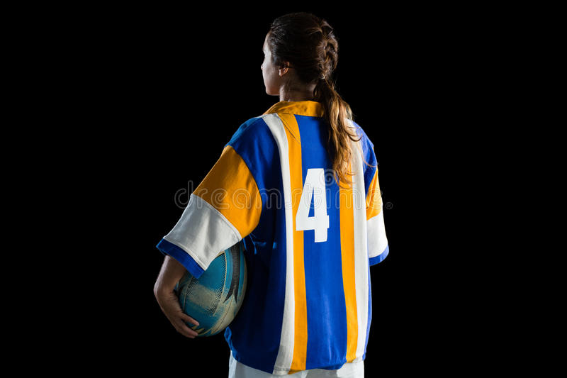 Rear view of female athlete holding rugby ball. While standing against black backgrond royalty free stock photos