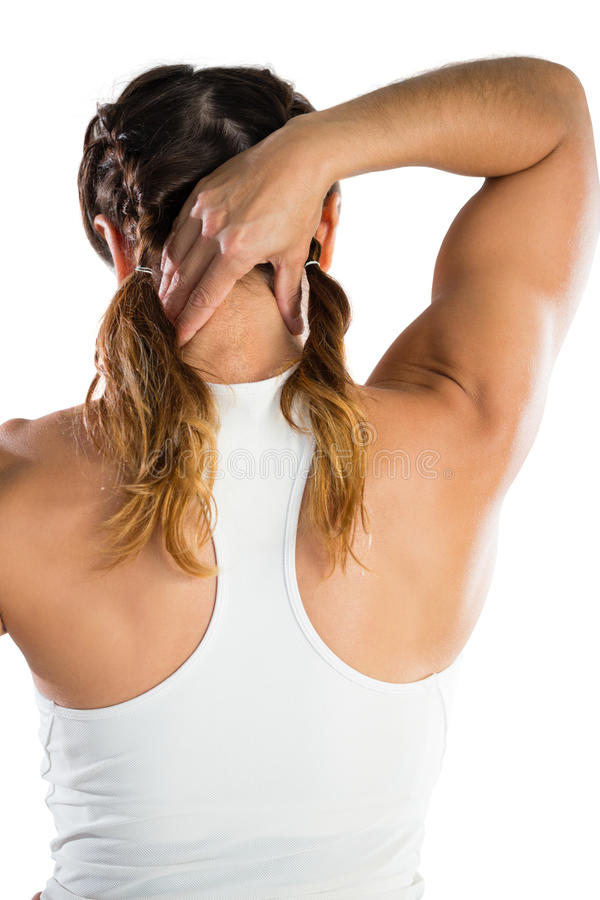 Rear view of female athlete massaging neck. While standing against white background stock photo