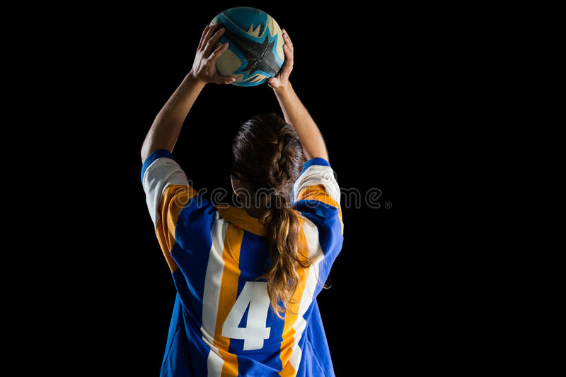 Rear view of female athlete playing rugby. Against black background stock photos