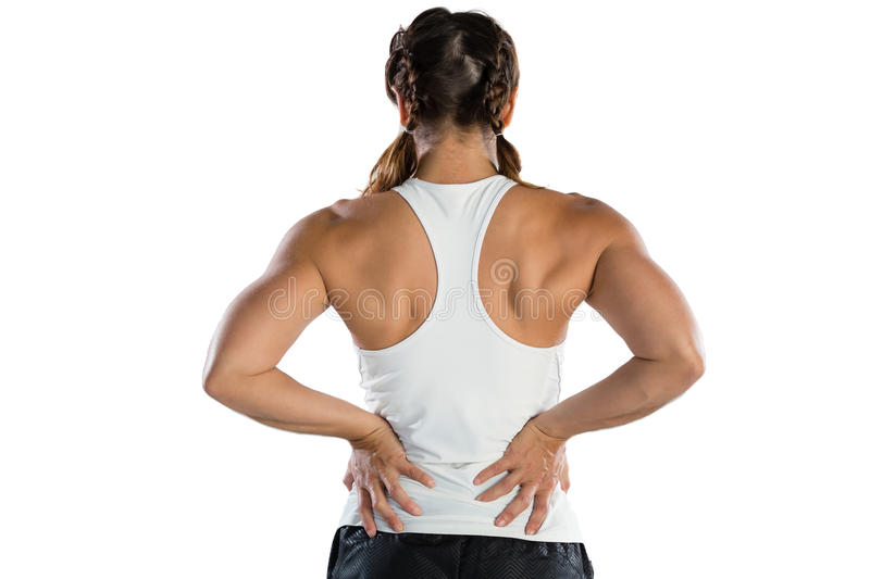 Rear view of female athlete suffering from back pain. While standing against white background stock photo