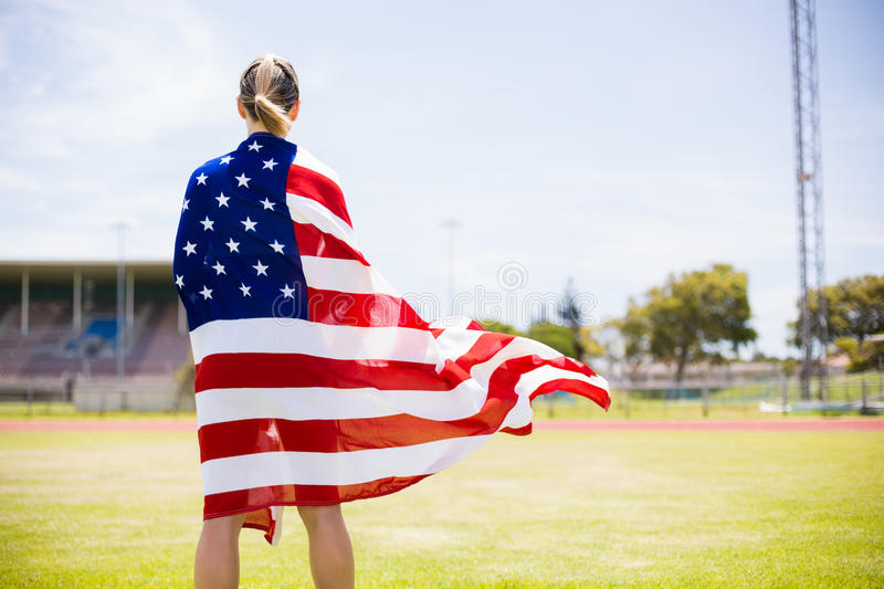 Rear view of female athlete wrapped in american flag stock photos