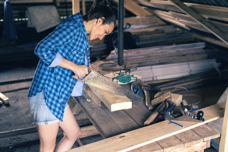 Rear view of a female carpenter sawing with a hacksaw boards, woodworking at home royalty free stock photography