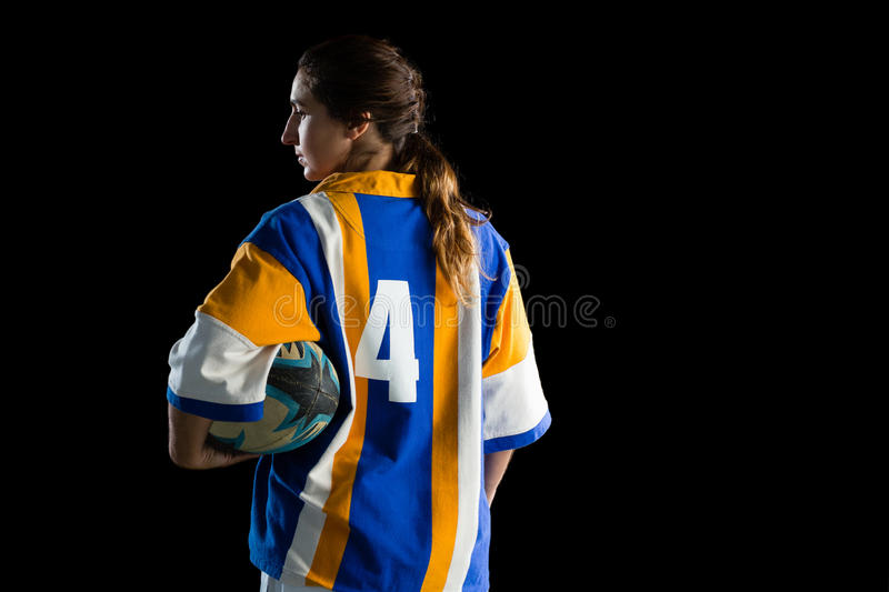Rear view of female player holding rugby ball. While standing against black background stock images