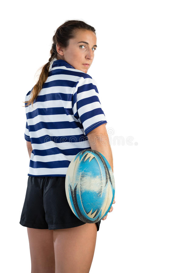 Rear view of female player with rugby ball. Standing against white background stock photo