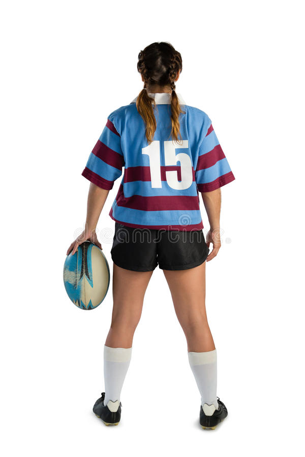 Rear view of female rugby player with rugby ball. Standing against white background stock photos