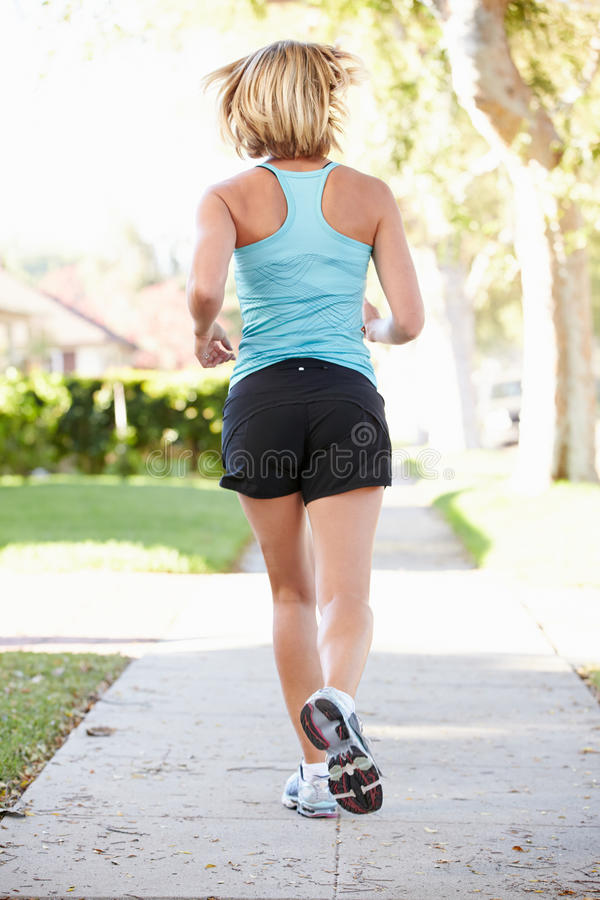 Download Rear View Of Female Runner Exercising On Suburban Street Royalty Free Stock Images - Image: 31347789