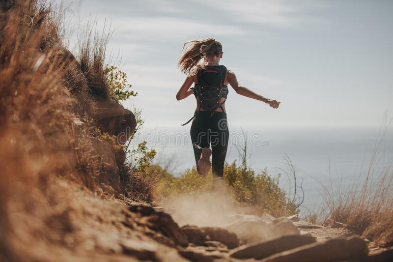 Female running over rocky trails on the hillside. stock photography