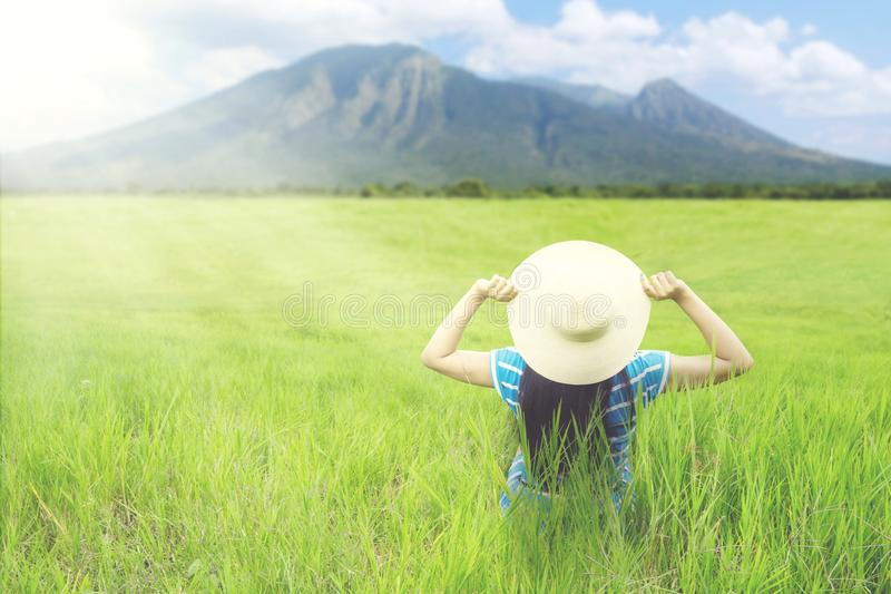 Female tourist admiring mountain view. Rear view of female tourist sitting on the meadow while admiring mountain view stock photography
