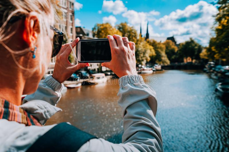 Rear view of female tourist taking photo of canal in Amsterdam on the mobile phone on sunny autumn day. Warm gold. Afternoon sunlight. Travel in Europe royalty free stock photos