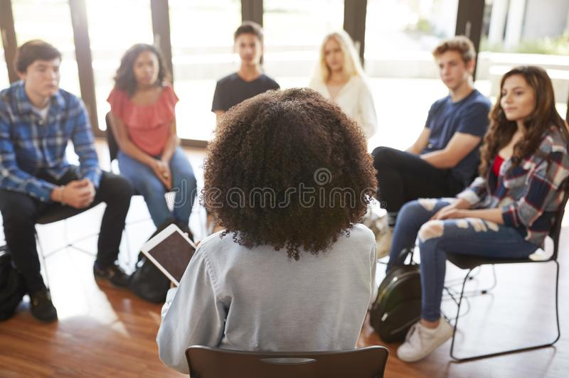Rear View Of Female Tutor Leading Discussion Group Amongst High School Pupils stock photo