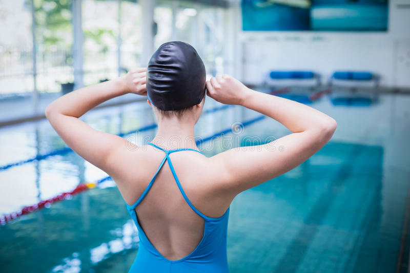 Rear view of fit woman putting on swim cap. At the pool stock images