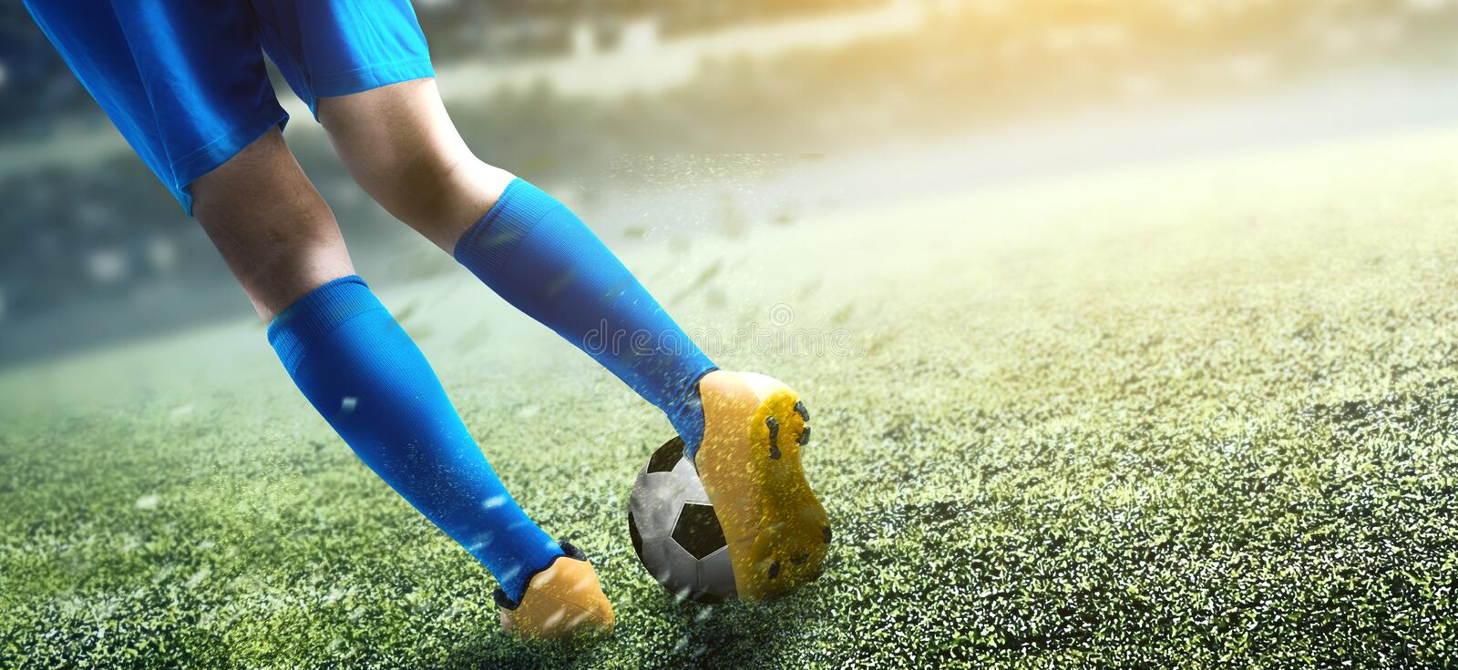 Rear view of football player man kicking the ball. On the football field at stadium stock images