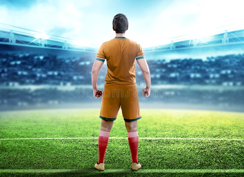 Rear view of football player man standing in the middle of football field. On stadium stock image