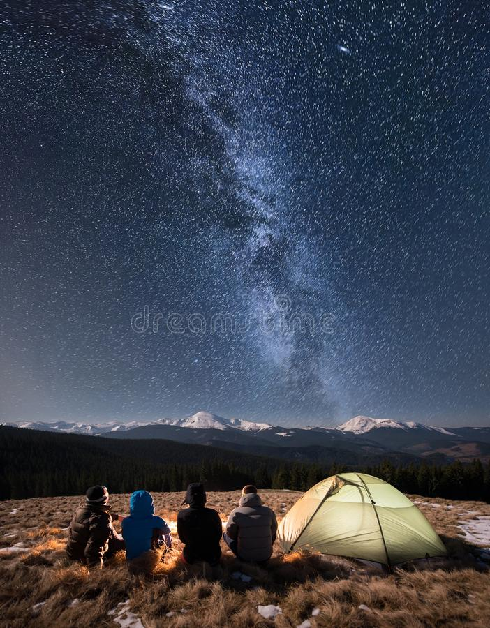 Rear view of four people sitting together beside camp and tent under beautiful night sky full of stars and milky way. On the background snow-covered mountains royalty free stock image
