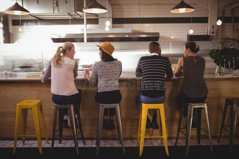 Rear view of friends sitting on stool at counter stock photos