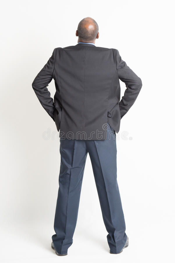 Rear view full length mature Indian businessman looking up stock photo