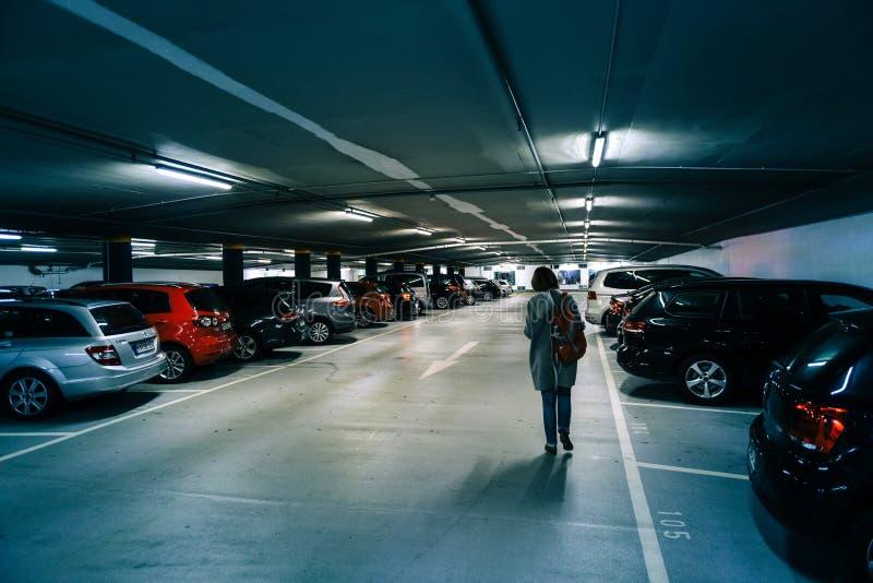 Rear view of German woman walking toward car. Karlsruhe, Germany - Oct 29, 2017: Rear view of German woman walking toward car in new underground parking in stock images